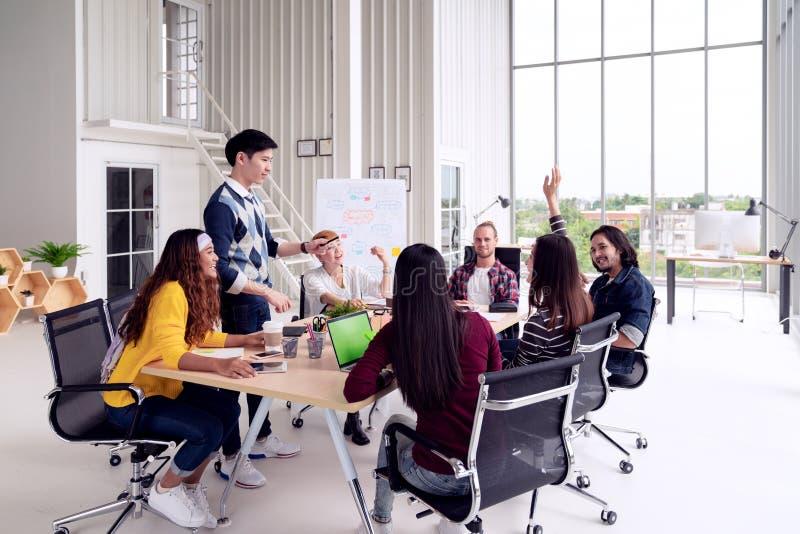 谈话,笑和群策群力在会议的小组多种族年轻创造性的队在现代办公室概念 女性身分 免版税库存照片
