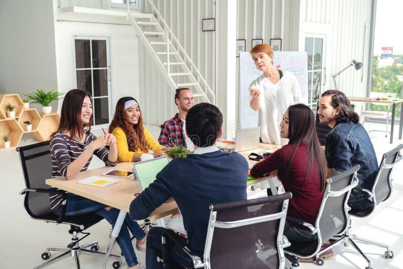 谈话,笑和群策群力在会议的小组多种族年轻创造性的队在现代办公室概念 免版税图库摄影
