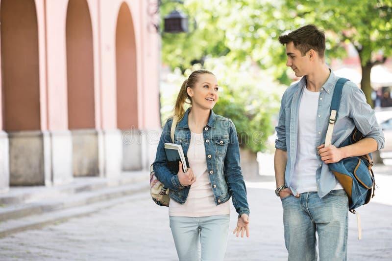 谈话年轻学院的朋友,当走在校园时 免版税库存照片