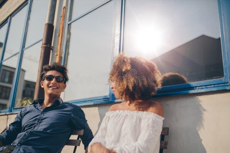 谈话年轻的夫妇坐户外和 图库摄影