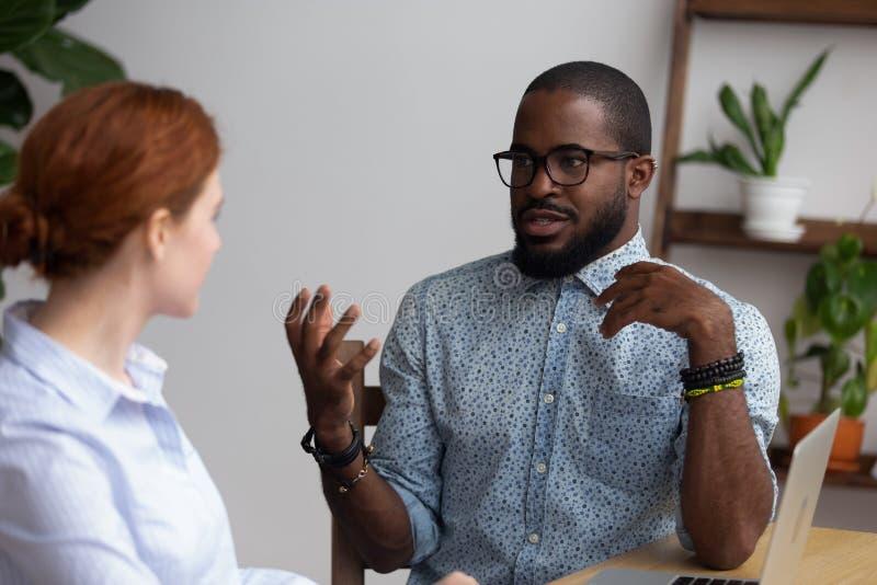 谈黑人和白种人的队友在办公桌的开会 库存图片