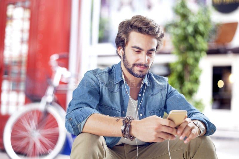 谈年轻的人在街道的手机 免版税库存图片