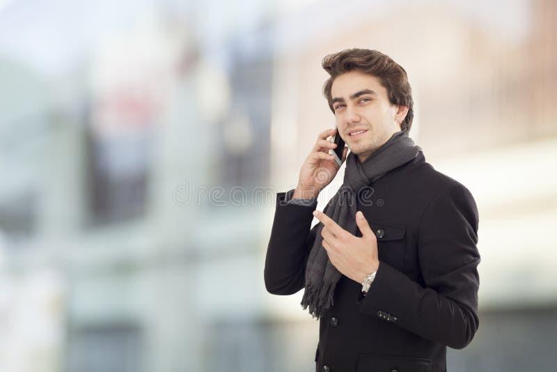 谈年轻的商人在街道上的手机 图库摄影