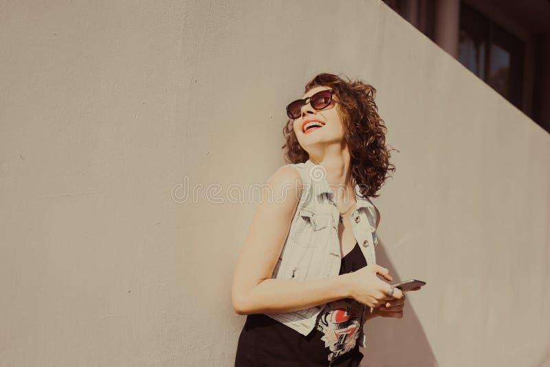 谈年轻美丽的卷曲深色的女孩画象太阳镜的有红色嘴唇的电话做selfi 免版税图库摄影