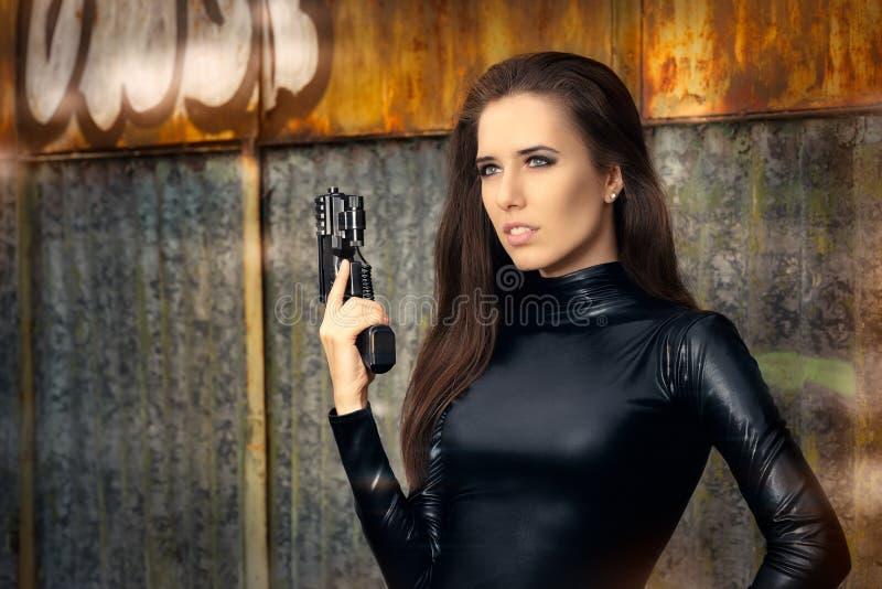 间谍拿着枪的黑皮革衣服的代理妇女 免版税库存照片