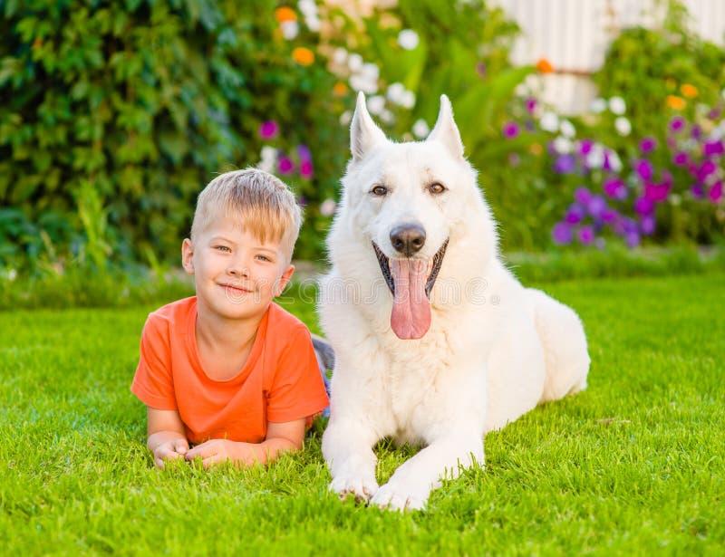 说谎与在绿草的白色瑞士牧羊犬的年轻男孩 免版税库存图片