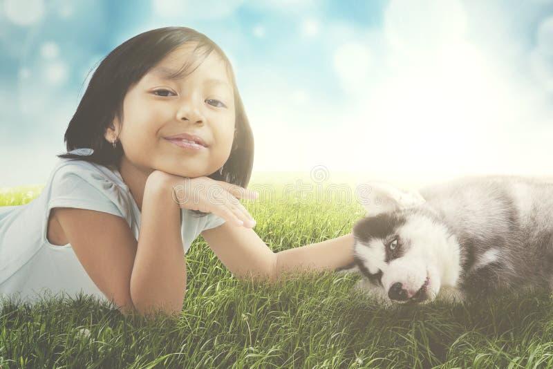 说谎与多壳的小狗的逗人喜爱的女孩 免版税库存照片