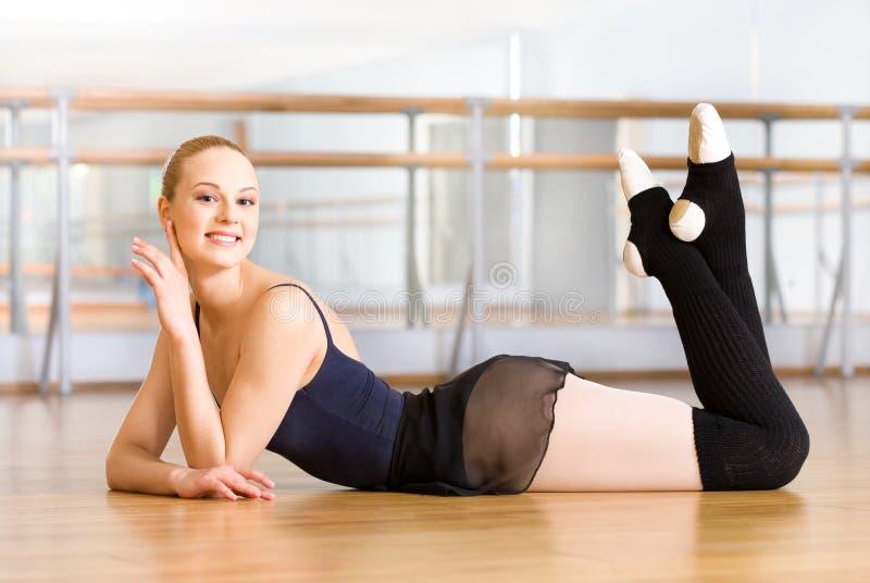 说谎与她的腿的芭蕾舞女演员在地板上 免版税库存照片