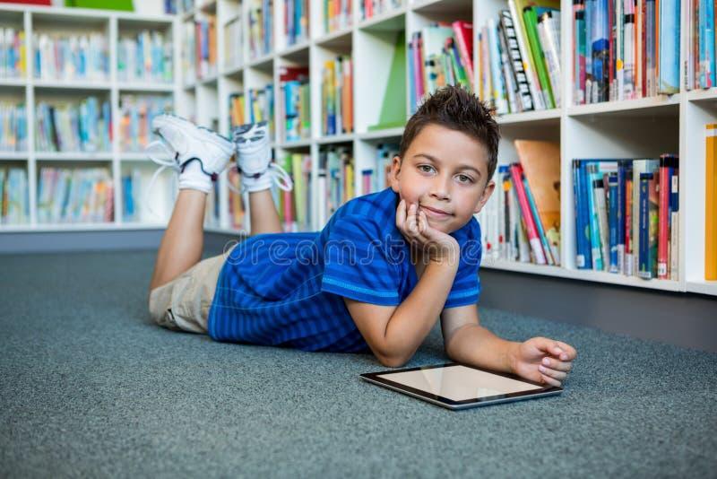 说谎与数字式片剂的男孩在学校图书馆里 库存图片