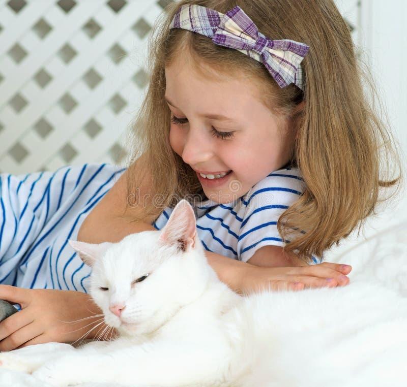 说谎与猫的小女孩 图库摄影
