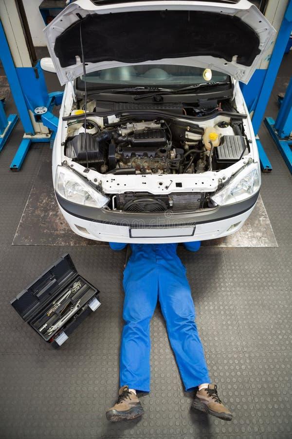 说谎和工作在汽车下的技工 免版税图库摄影