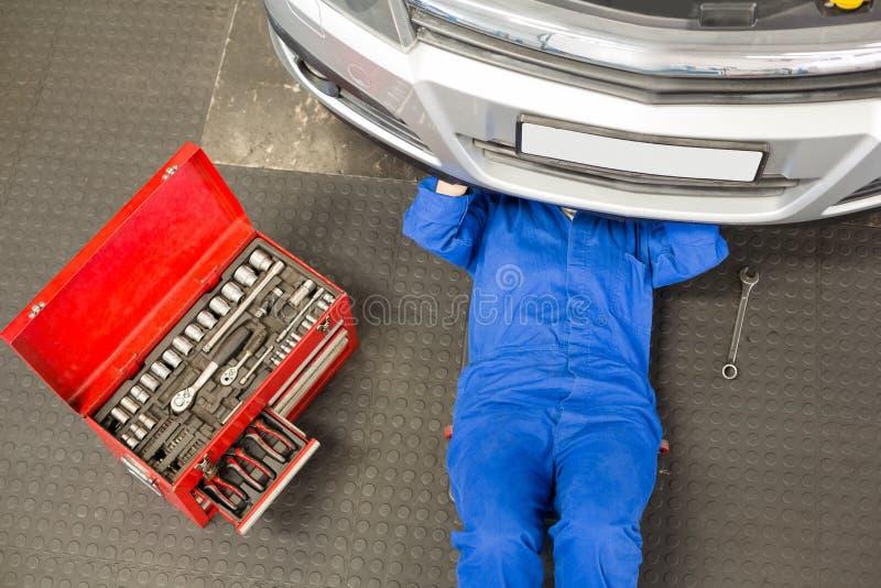 说谎和工作在汽车下的技工 库存照片