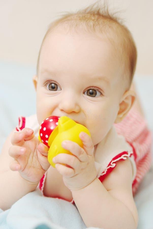 说谎和舔玩具的逗人喜爱的婴孩 库存照片
