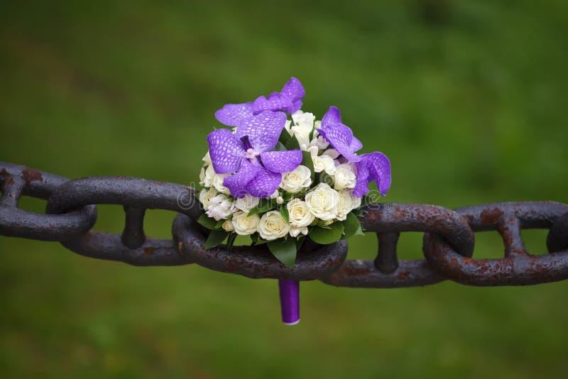 说谎在一个古老生锈的链子的婚礼花束 图库摄影