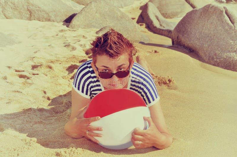 说谎在一个沙滩的妇女的葡萄酒照片 免版税库存图片