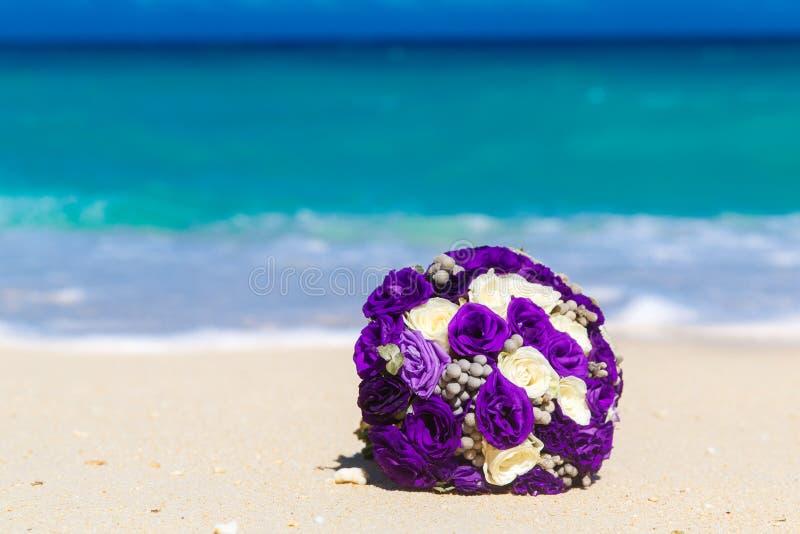 说谎在一个热带海滩的沙子的婚礼花束 蓝色海运 库存照片