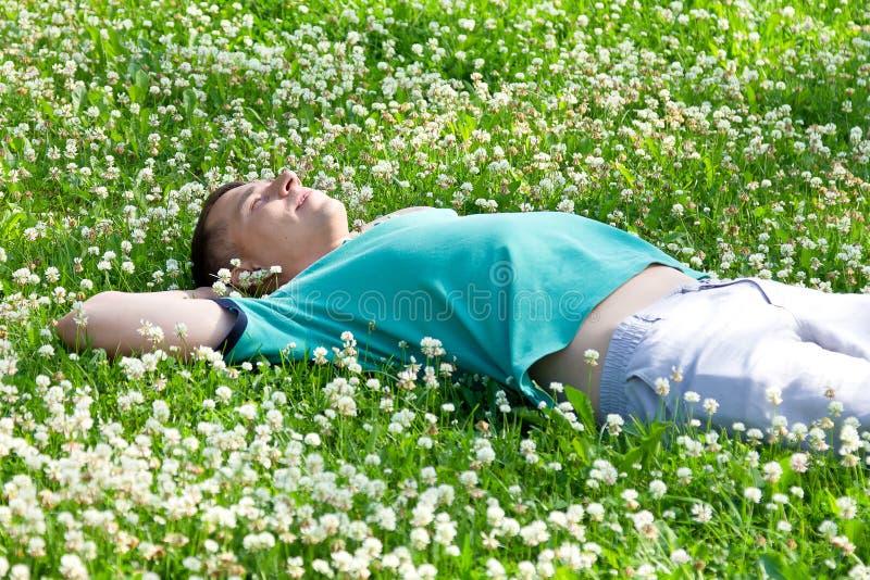 说谎在一个绿色夏天草甸的愉快的正面人 免版税图库摄影