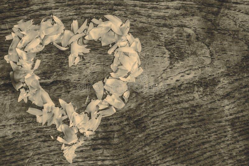 从说谎在一张木桌上的瓣的心脏 免版税图库摄影