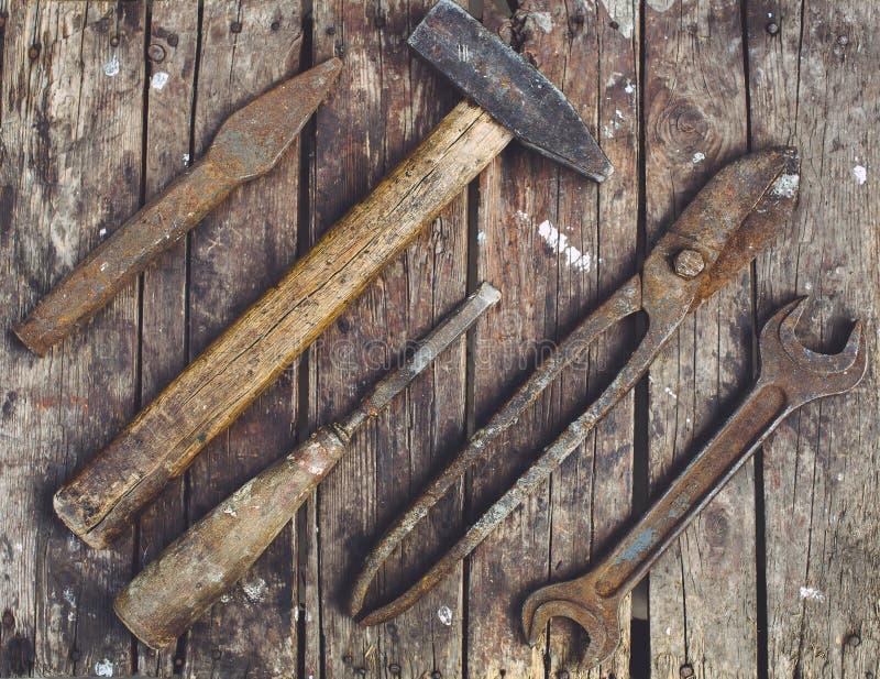说谎在一张木桌上的老,生锈的工具 图库摄影