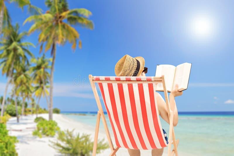 说谎在一本室外椅子和阅读书的年轻人,在海滩 免版税库存照片