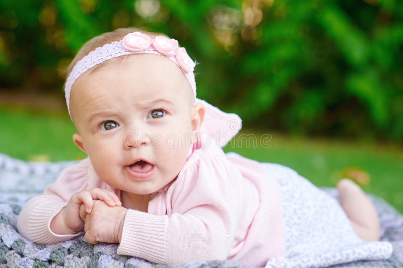 说谎在一条毯子的小女婴在草的一个公园 库存图片