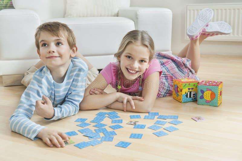 说谎在与卡片的地板上的女孩和弟弟的画象 库存图片