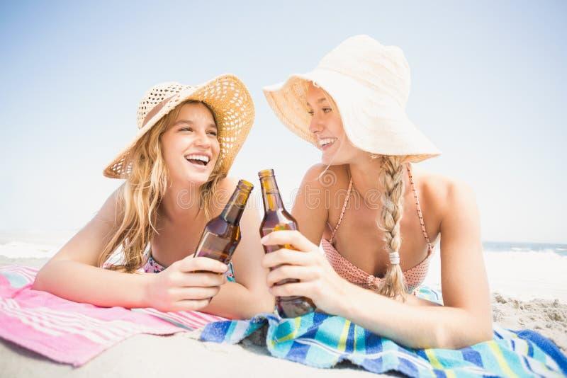 说谎在与啤酒瓶的海滩的愉快的妇女 库存照片