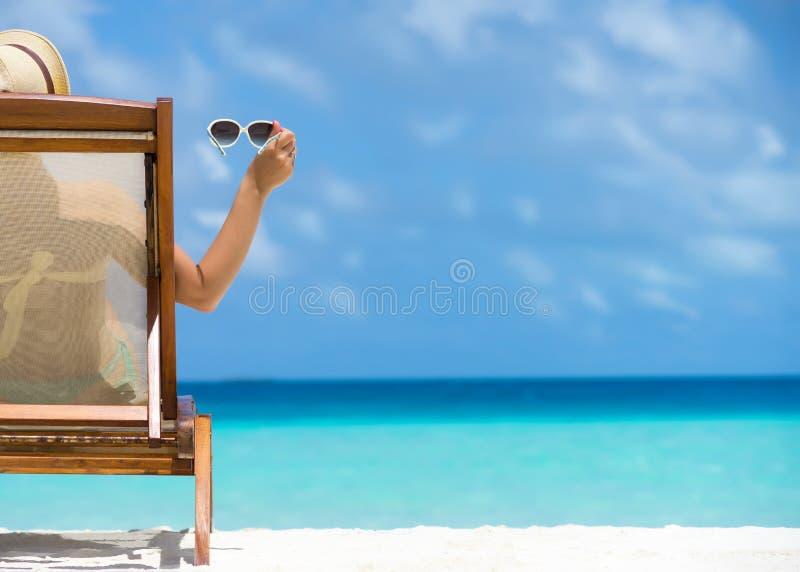 说谎在与在手中玻璃的一个海滩懒人的女孩 免版税库存图片