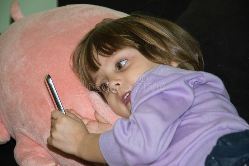 说谎在与她的被充塞的玩具猪和手机的床上的逗人喜爱的小女孩 免版税库存图片