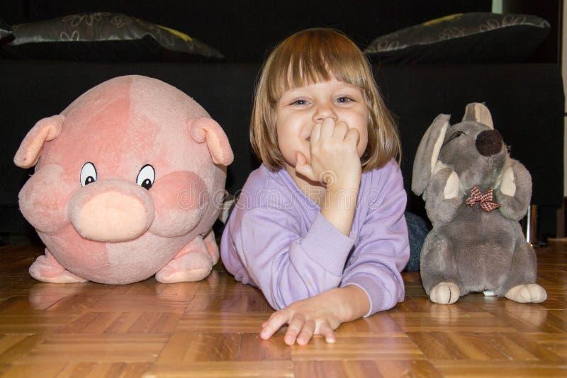 说谎在与她的被充塞的玩具猪和老鼠的地板上的逗人喜爱的小女孩 免版税库存图片