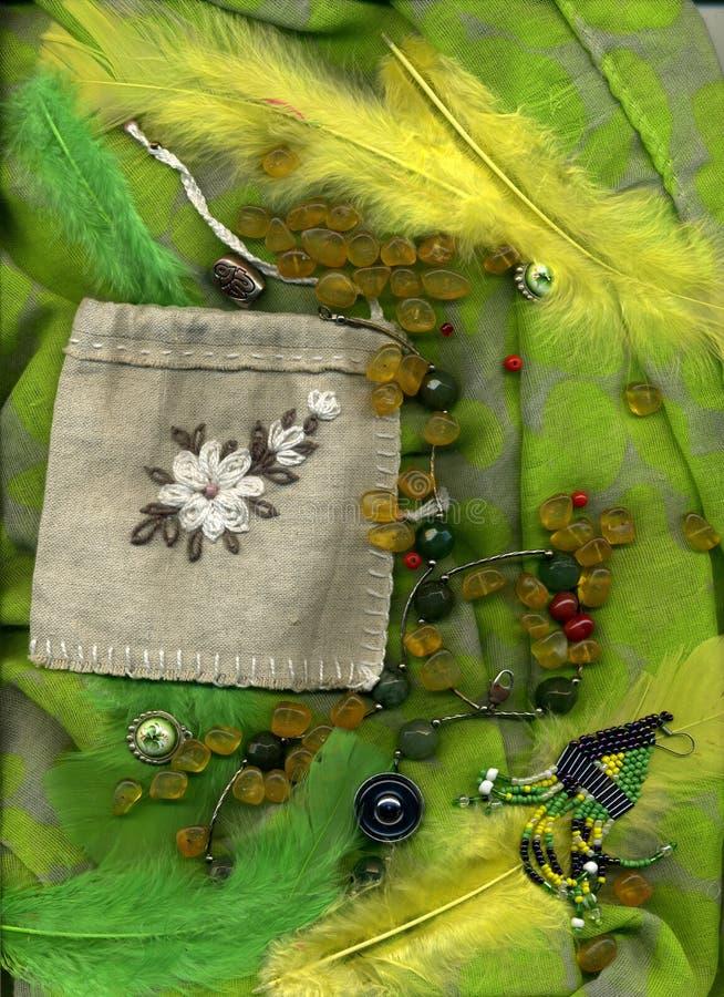 说谎在与按钮、羽毛和首饰的绿色纺织品的琥珀色的小珠 向量例证
