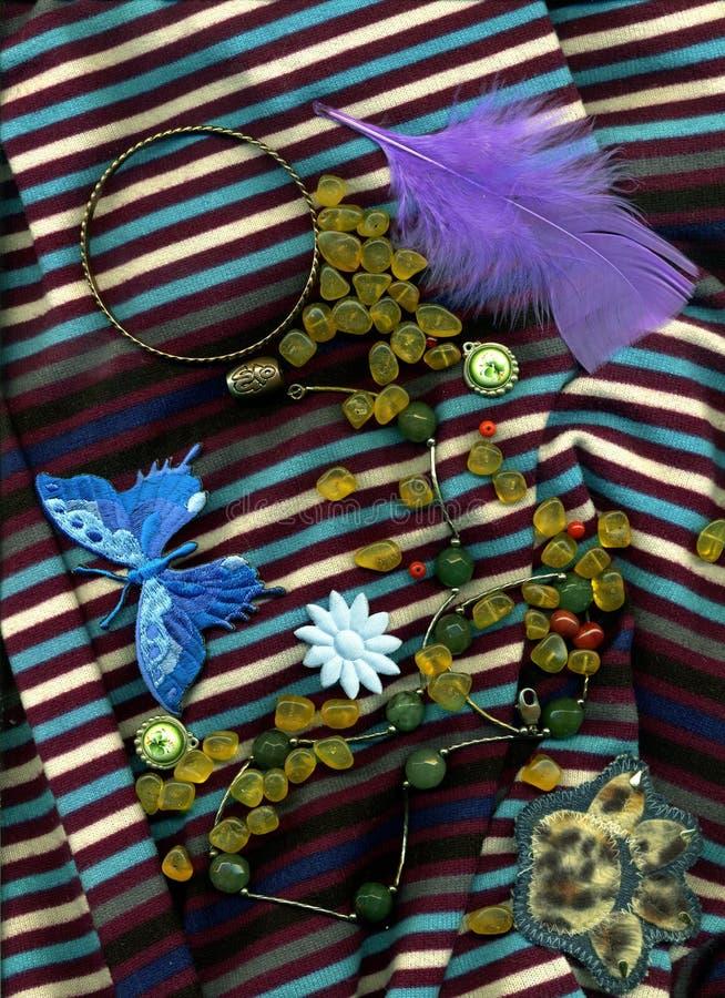 说谎在与按钮和针设计的镶边布料的琥珀色的小珠 免版税库存照片
