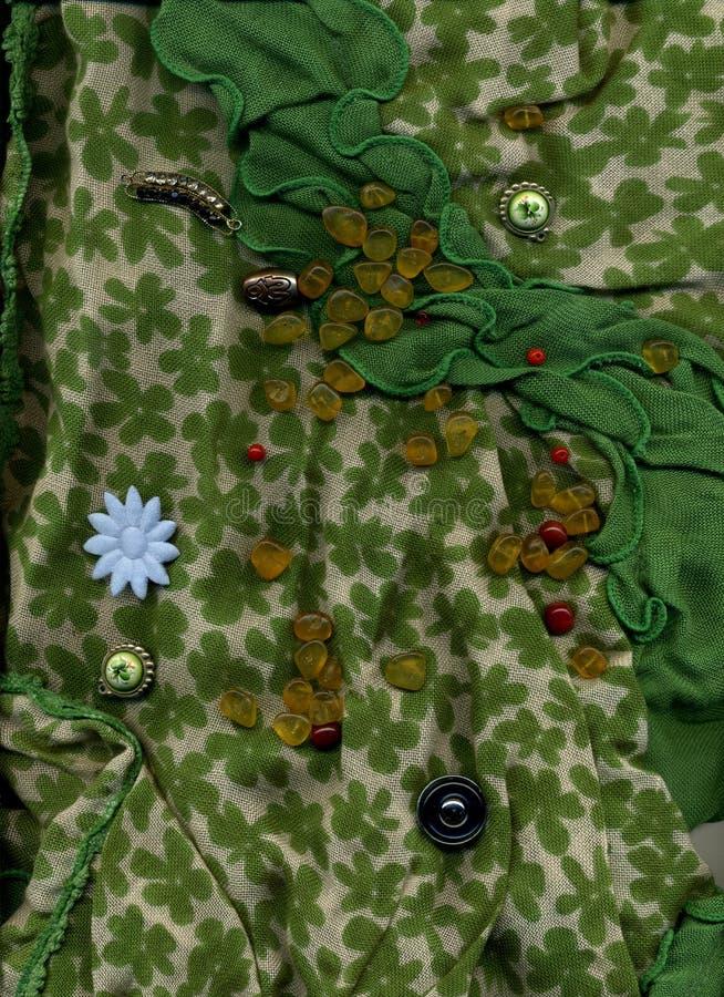 说谎在与按钮的绿色纺织品的琥珀色的小珠 免版税图库摄影