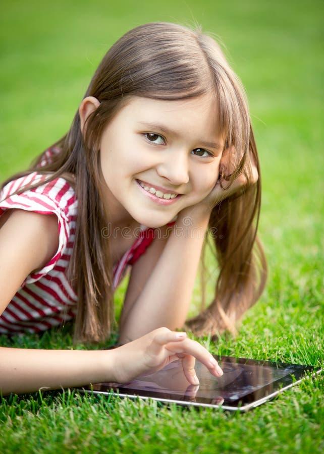 说谎在与数字式片剂的草的逗人喜爱的微笑的女孩画象  库存图片