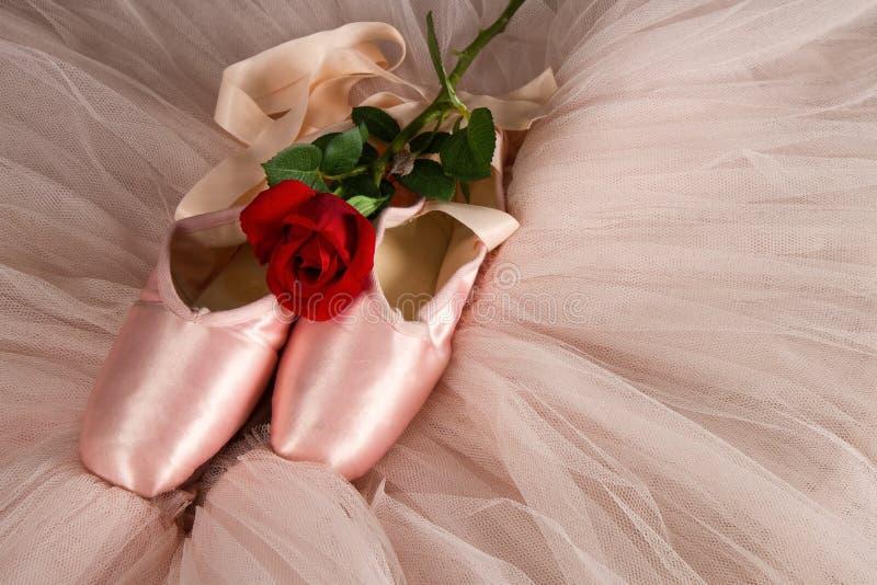 说谎在与玫瑰色和芭蕾舞短裙的地板上的老使用的芭蕾拖鞋 免版税库存照片