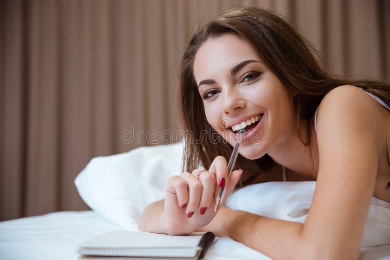说谎在与笔和笔记薄的床上的妇女 免版税库存图片