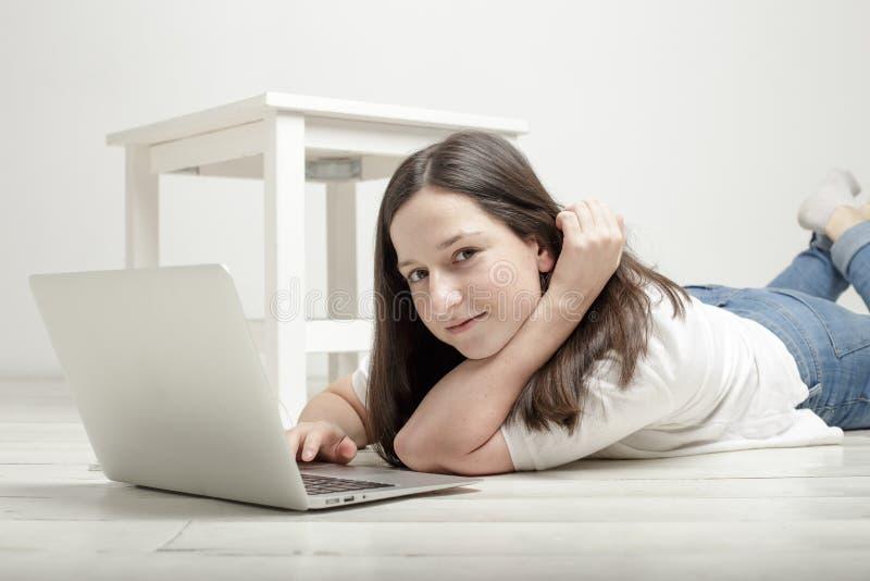 说谎在与膝上型计算机和smilin的地板上的美丽的女孩 图库摄影