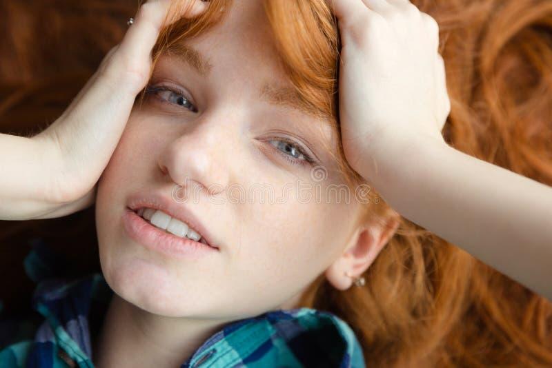 说谎在与被弄乱的头发的地板上的逗人喜爱的女孩特写镜头 免版税库存图片