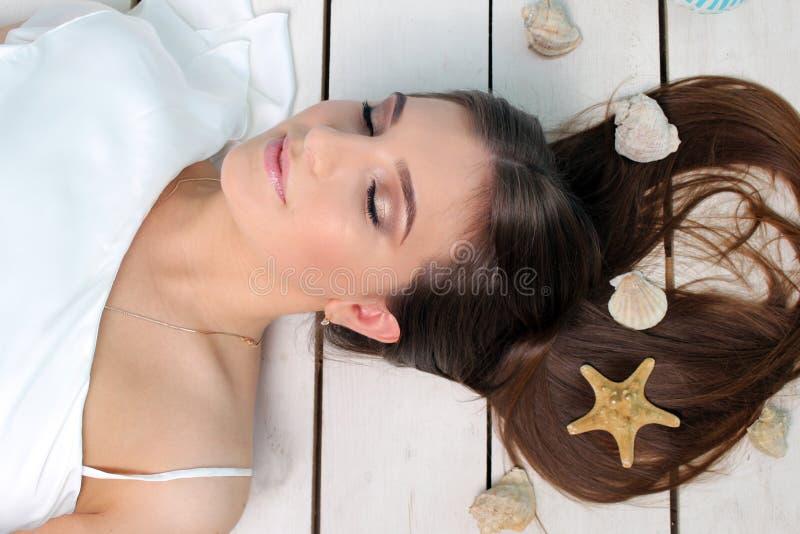 说谎在与贝壳的地板上的美丽的女孩在她的头发 画象 工作室 库存照片