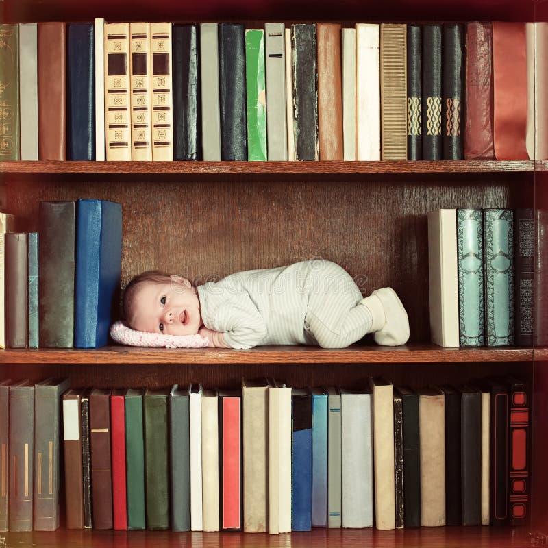 说谎在书橱的书架的婴孩 免版税库存照片