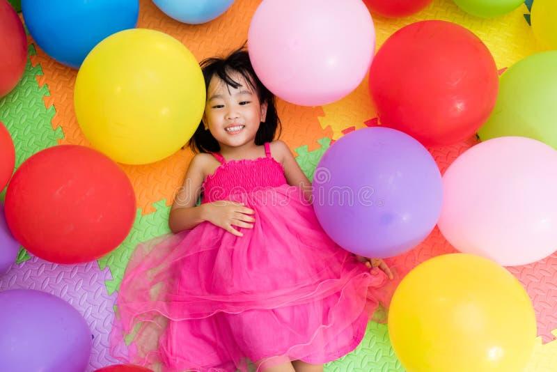 说谎在五颜六色的Ba中的地板上的亚裔矮小的中国女孩 免版税库存照片