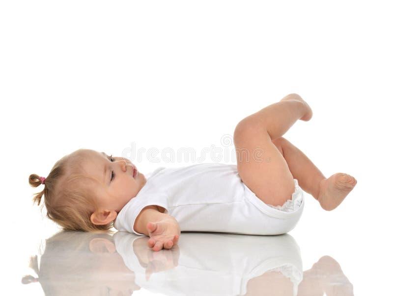 说谎在后面和looki的尿布的滑稽的婴儿儿童女婴 库存照片