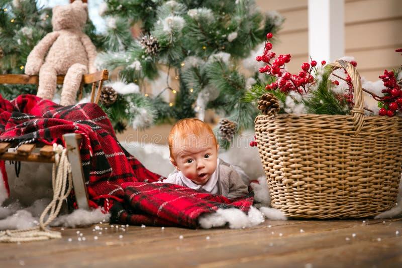 说谎在圣诞节装饰中的地板上的逗人喜爱的男婴 免版税库存照片