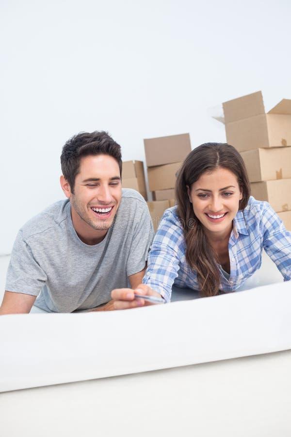 说谎在地板上和举行房子计划的愉快的夫妇 库存图片