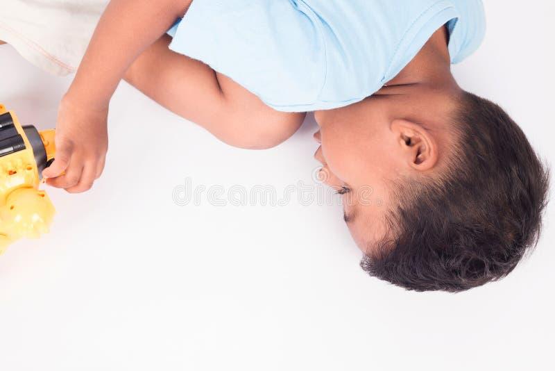 说谎在地板上和演奏玩具的儿童亚裔小男孩 免版税库存照片