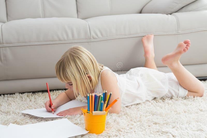 说谎在地板上的微笑的litlle女孩图画 免版税库存照片