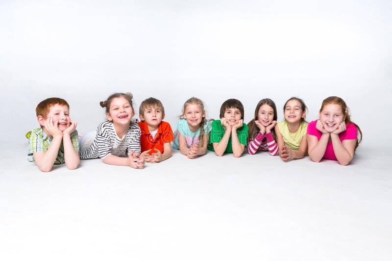 说谎在地板上的愉快的孩子在演播室,拷贝空间 免版税库存照片
