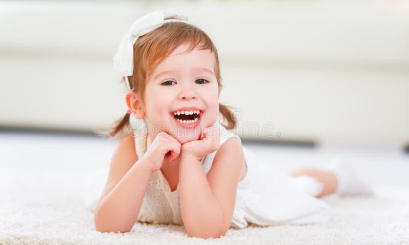 说谎在地板上的愉快的小女孩在一个绝尘室 免版税库存照片