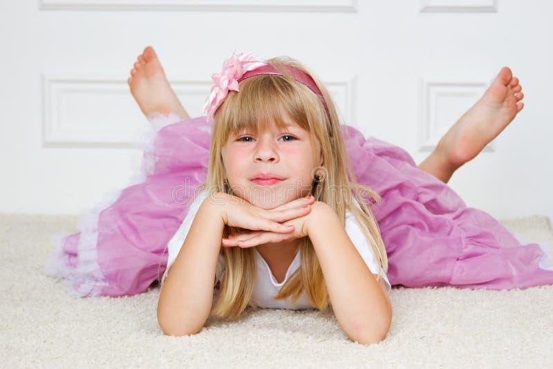 说谎在地板上的美丽的女孩 免版税库存图片
