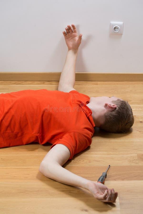 说谎在地板上的被触电致死的人 免版税库存照片